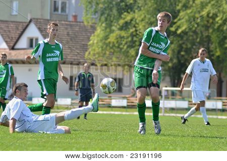 KAPOSVAR, HUNGARY - SEPTEMBER 5: Arpad Horvath (white 17) in action at the Hungarian National Championship under 19 game Kaposvar (white) vs. Nagyatad (green) September 5, 2011 in Kaposvar, Hungary.