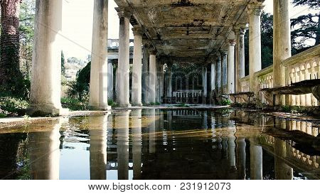 Slow Motion Stone Falls Into A Puddle In An Old Beautiful Building With Columns