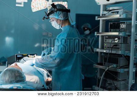 Side View Of Surgeon Operating Patient In Operating Room