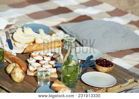 Fruits, fresh bread, sandwiches, bottle and glasses of homemade lemonade and cherries in wooden bowl prepared for party or picnic on the beach