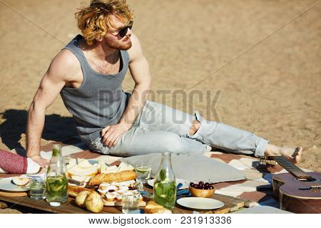 Young man in sunglasses, vest and jeans sitting on sand by served place with snack