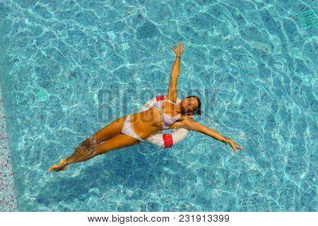 Beautiful tanned woman in blue swimwear relaxing in swimming pool spa.