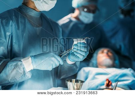 Cropped Image Of Surgeon Cleaning Surgical Tweezers In Surgery Room