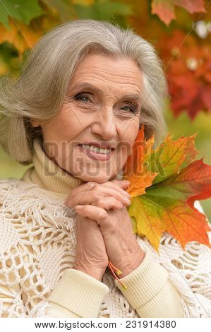 Portrait Of Senior Beautiful Woman Holding Autumn Leaves