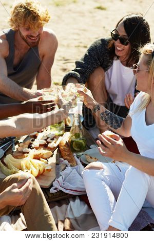 Several young friends toasting with glasse sof lemonade over snack during picnic on beach