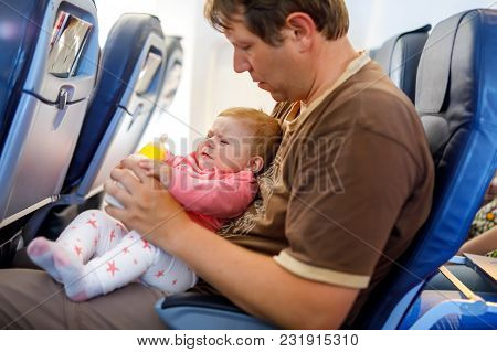Father Holding Baby Daughter During Flight On Airplane Going On Vacations. Baby Girl Drinking Formul