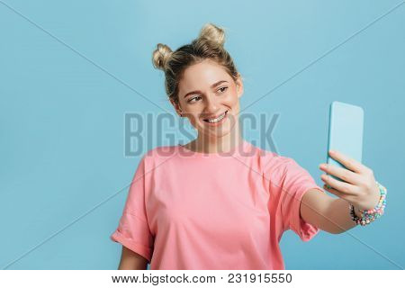 Youth Trendy Woman Making Photo On Her Smartphone Against A Blue Pastel Background . Making Cool Sel