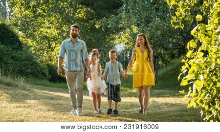 Full length view of a happy family with two children wearing casual summer clothes while holding hands during recreational walk in the park