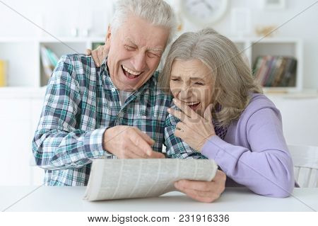 Close-up Portrait Of A  Senior Couple With Newspaper  At Home