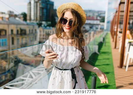Cute Girl With Long Hair  In Sunglasses Is Standing On The Terrace. She Wears A White Dress With Bar