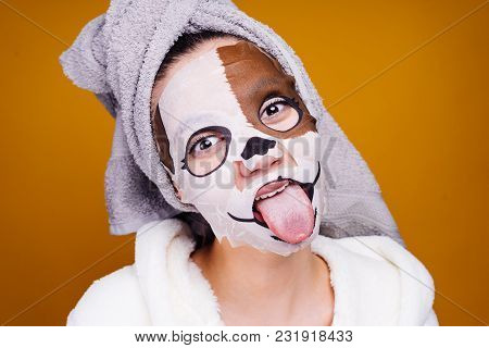 Young Girl With A Towel On Her Head, On Her Face A Mask With A Picture Of A Muzzle Of A Dog, Shows A
