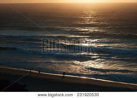Dark Early Sunrise At The Indian Ocean Beach, Seascape, Landscape With Silhouettes Of People Walking