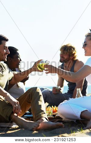 One of guys pouring lemonade from bottle to glass of girl during picnic by seaside