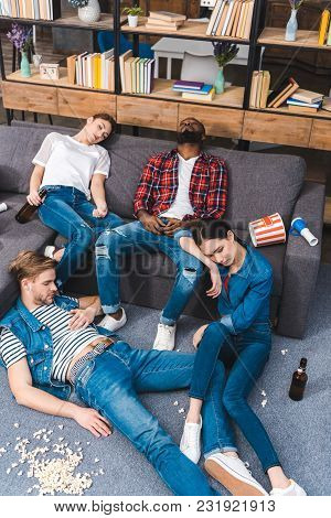 High Angle View Of Young Multiethnic Friends Sleeping In Messy Room With Popcorn And Beer Bottles