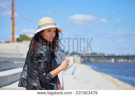 Portrait of happy smiling woman standing on the square on sunny summer or spring day outside, cute smiling woman looking at you,
