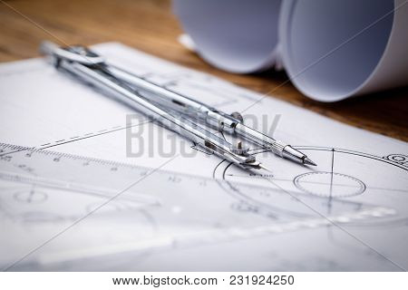 Architectural Blueprints And Blueprint Rolls And A Drawing Instruments On The Worktable. Drawing Com