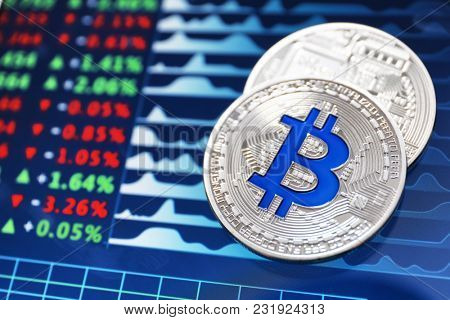 Silver bitcoins on screen with exchange rates. Finance trading