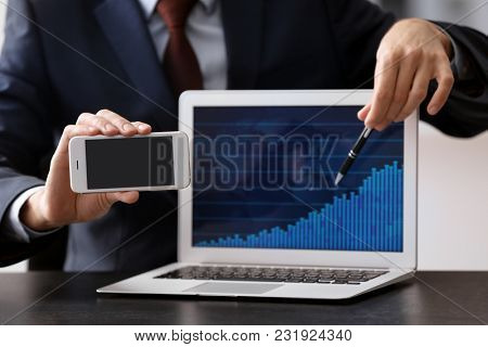 Man holding smartphone near laptop with stock chart data on screen. Forex concept