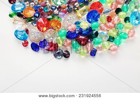 Jewellery with colorful precious stones on white background