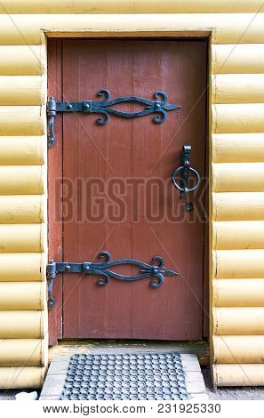 Traditional Russian Wooden Door With Forged Massive Metal Hinges In The House From Logs