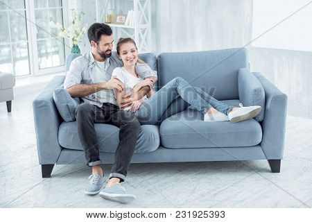 Feel My Support. Pretty Girl Keeping Smile On Her Face And Sitting On The Couch While Leaning On Her