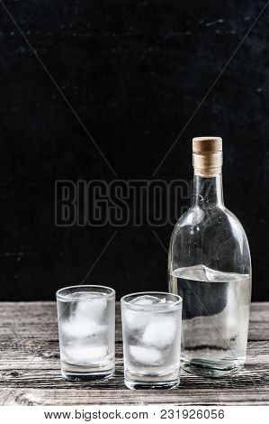Cold Vodka In Shot Glasses On A Black Background On Wooden Table Closeup With Copyspace Vertical Ima