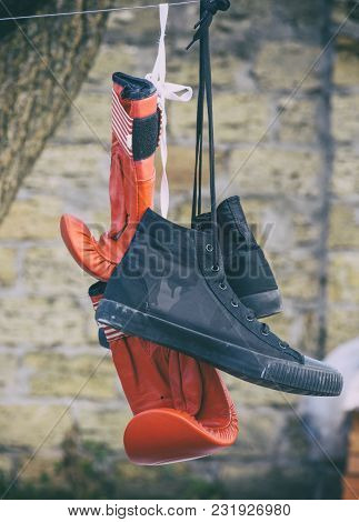 A Pair Of Red Boxing Gloves And A Pair Of Black Textile Sneakers Hanging On A Rope