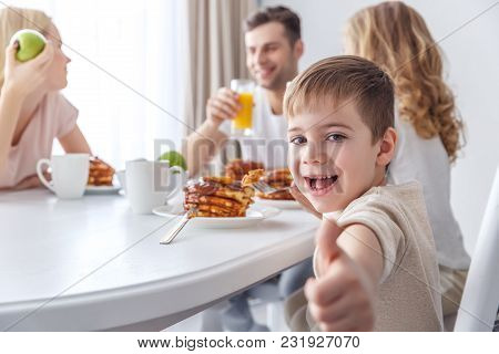 Little Kid Showing Thumb Up While Having Breakfast With Family