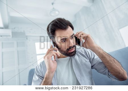 It Is Not Truth. Surprised Bearded Male Person Wrinkling Forehead While Holding Telephones Near Ears