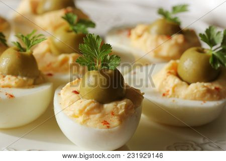 Spicy Deviled Eggs Garnished With Green Olives And Parsley .