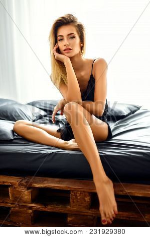 Natural Pretty Blonde Girl In Black Elegant Lace Lingerie Sitting On Bed In Bright Bedroom