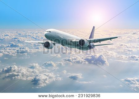Passenger Airplane Flying Above Clouds. View From The Window Plane To Amazing Sky At The Sunset.