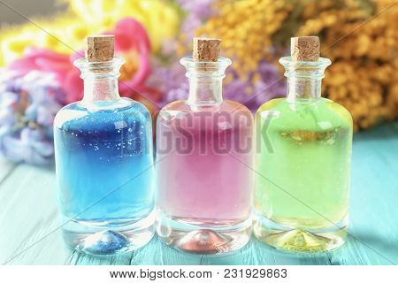 Bottles with different perfume oils on wooden table