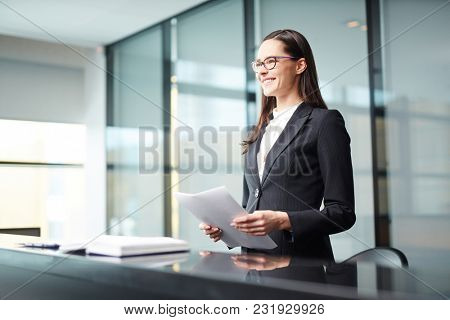 Young businesswoman or delegate with papers making report at conference or political summit