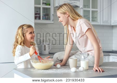 Adorable Young Daughter Helping Mother To Cook Breakfast
