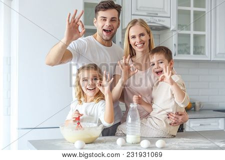 Young Family Cooking Breakfast Together And Showing Okay Sign