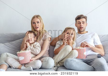 Frightened Young Family Watching Scarry Movie On Couch At Home