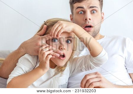 Shocked Father And Daughter Watching Scarry Movie Together
