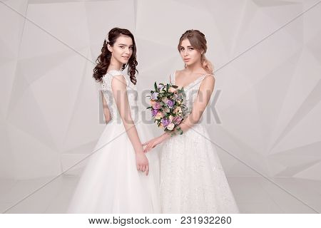 Two Adorable Ladies Wearing In Long Fashionable Dresses Holding Flowers.
