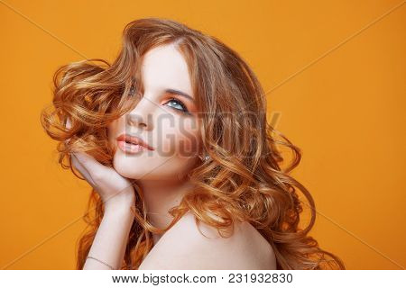 Beautiful Redheaded Girl With Luxurious Curly Hair. Studio Portrait On Yellow Background. Luxuriant