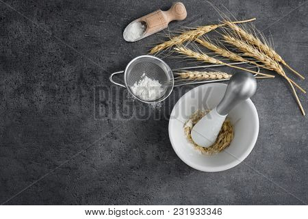 Cooking utensils, wheat spikes and flour on grey background