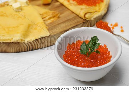 Bowl with delicious red caviar on white wooden table