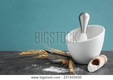 Cooking utensils, wheat spikes and flour on table