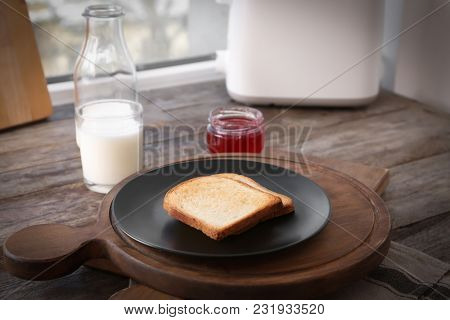 Plate with toasted bread on table