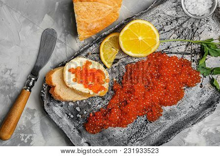 Composition with red caviar and tasty sandwiches on table