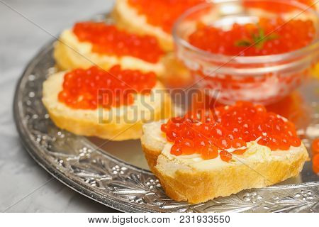 Tasty sandwiches with red caviar on vintage metal tray, closeup