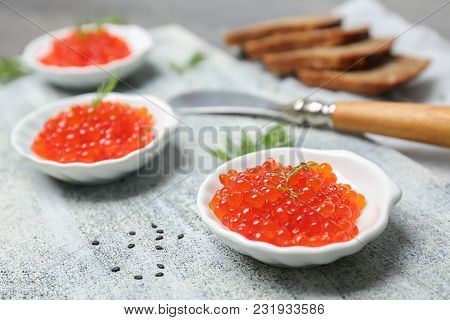 Little plates with delicious red caviar on table