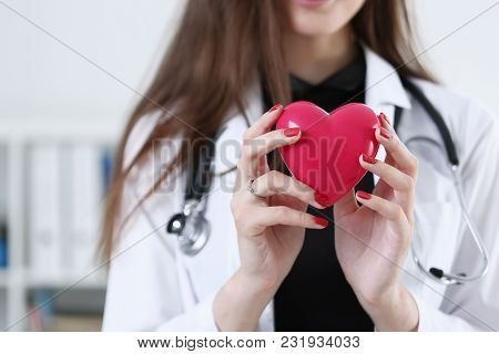 Female Medicine Doctor Hands Holding And Covering Red Toy Heart Closeup. Cardio Therapeutist Student