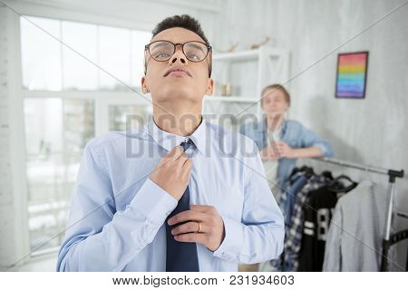 Everything Perfect. Meditative Earnest Focused Man Touching Tie While Wearing Glasses And Looking Up