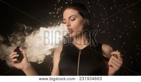 Brunette Woman Vaping Electronic Cigarette With Smoke On Black Background Closeup. Young Woman Smoki